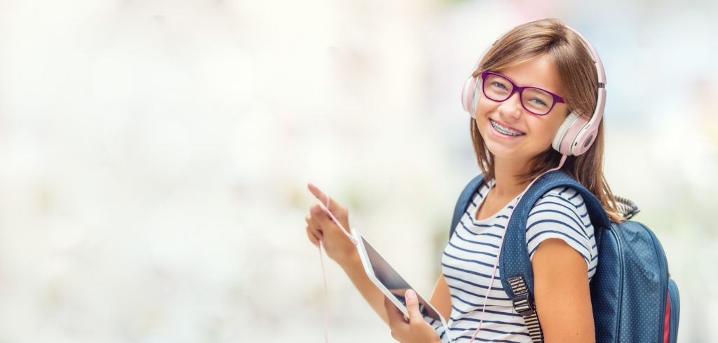 Portrait of modern happy teen school girl with dental braces glasses bag backpack headphones and tablet.