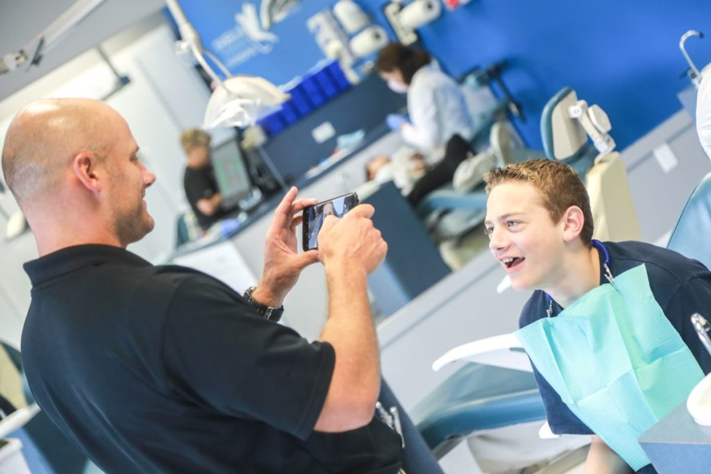 Patient's dad taking a photo of son's smile